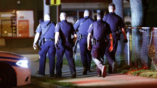 RPD officers search the area of Hudson and Clifford avenues after an officer was shot near the face earlier.
