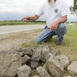 """The pile of asphalt along Fowlerville Road was collected by Conway Township resident Randy DeFaut from his property after grading three weeks ago. Regarding whose responsibility it is to maintain the runoff area, DeFaut says he's had it explained to him it's shared responsibility. About that shared responsibility, DeFaut responds, """"Yes, you guys (the road commission) tear it up, and I've got to fix it."""""""