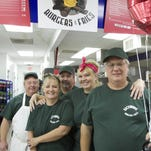 Members of the Backwoods Burgers & Fries crew, from left, cook John Schofer, cashier Tracey Jackson, co-owners Randy Cooley, Vikki and Allen Walblay celebrate their grand opening in the Genoa Township restaurant within the Sunoco station on Grand River.