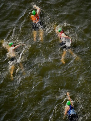 Racers swim in the Cumberland River during the Music City Triathlon in Nashville, Tenn., Sunday, July 27, 2014.