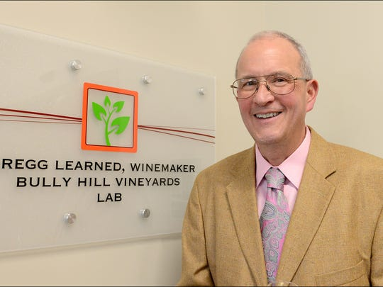 Gregg Learned, winemaker at Bully Hill, poses with the sign for the laboratory bearing his name at the Finger Lakes Community College Viticulture and Wine Center during a reception on April 10.