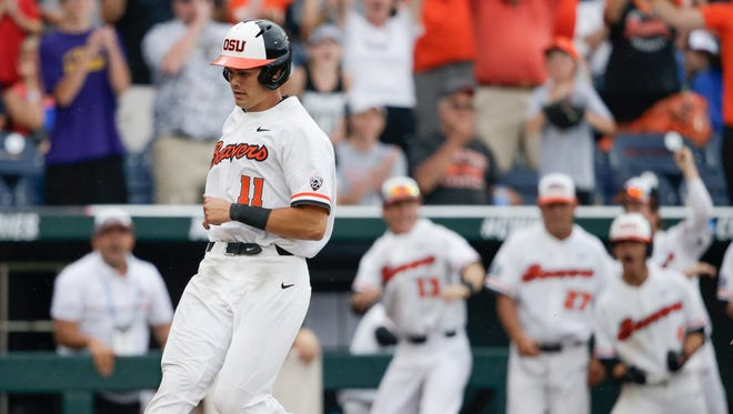 Oregon State designated hitter Trevor Larnach (11) scores the go-ahead run on a one-run single by Adley Rutschman against Cal State Fullerton in the eighth inning of an NCAA men's College World Series baseball game in Omaha, Neb., Saturday, June 17, 2017.