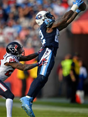 Titans tight end Delanie Walker (82) catches a pass over Texans cornerback Kareem Jackson (25) in the second half Sunday.