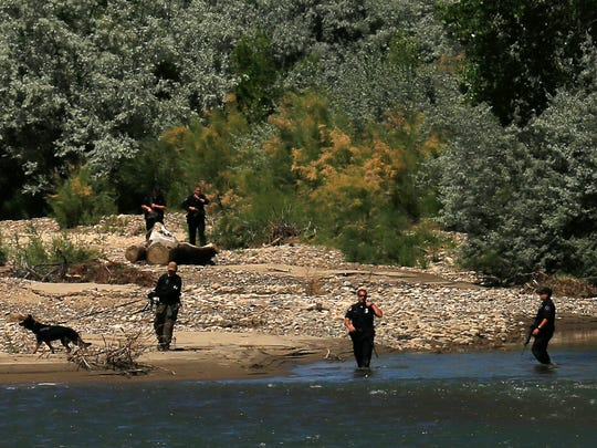 Law enforcement officers search along the Animas River in Farmington on Friday for a man suspected of trying to run over a police officer with his car.