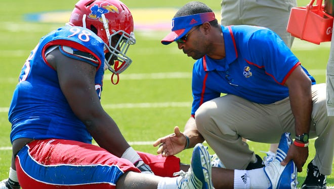 Murphy Grant, head athletic trainer at the University of Kansas, talks with a player.