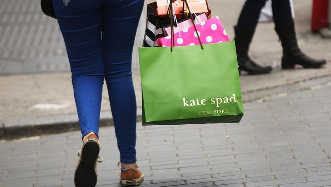 A woman walks out of a Kate Spade store in the SoHo neighborhood of Manhattan on May 8, 2017 in New York City.