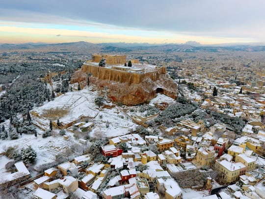 The Parthenon temple is seen atop of the snow-covered Acropolis hill in Athens, on Tuesday, Jan. 10, 2017. Snow closed schools in the capital, as added pressure on the government to speed up winter preparations for thousands of refugees living in camps around the country.