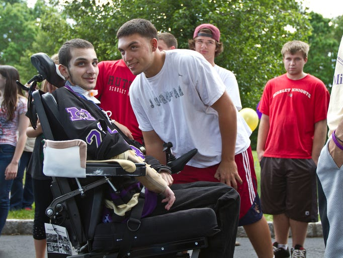 Mikey Nichols talks with Mario Danza, a friend and neighbor he has had since age 4.  Mikey Nichols, a Monroe High School hockey player who was paralyzed during a game this past winter, returned home. A large crowd of friends and community members greeted him as he arrived. Monroe Township, NJ Thursday, June 5, 2014 Doug Hood