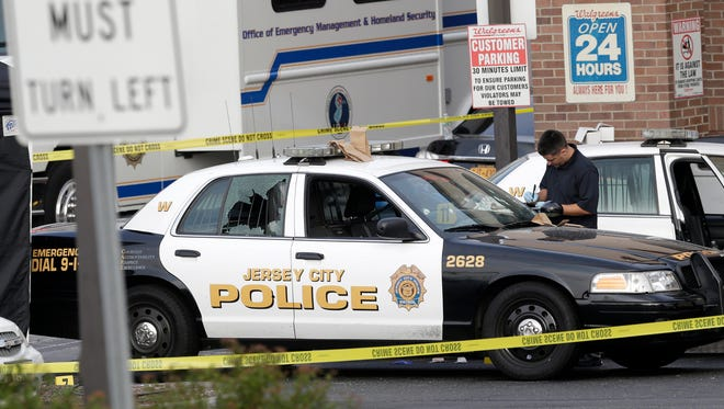 A Jersey City Police Department cruiser is seen with its back window shattered as officials investigate the scene where a Jersey City Police Department officer was shot and killed while responding to a call at a 24-hour pharmacy July 13, 2014, in Jersey City, N.J.