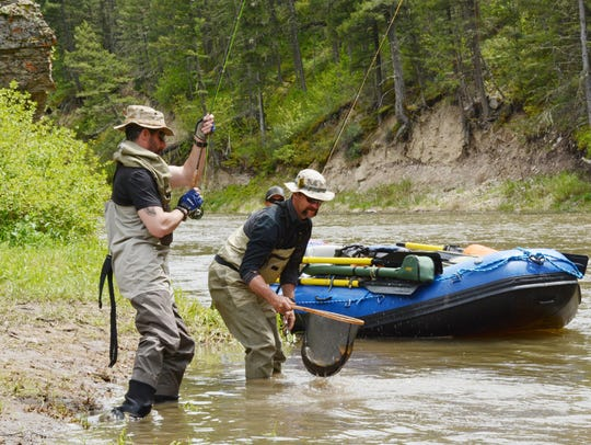 A guide helps his client bring in a fish, careful to