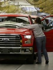 A worker inspects a new 2015 aluminum-alloy body Ford