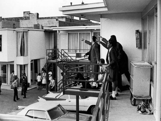 Dr. Ralph Abernathy and Jesse Jackson, both obscured, and others stand on the balcony of the Lorraine Motel and point in the direction of gunshots that killed American civil rights leader Dr. Martin Luther King Jr., who lies at their feet, on April 4, 1968.