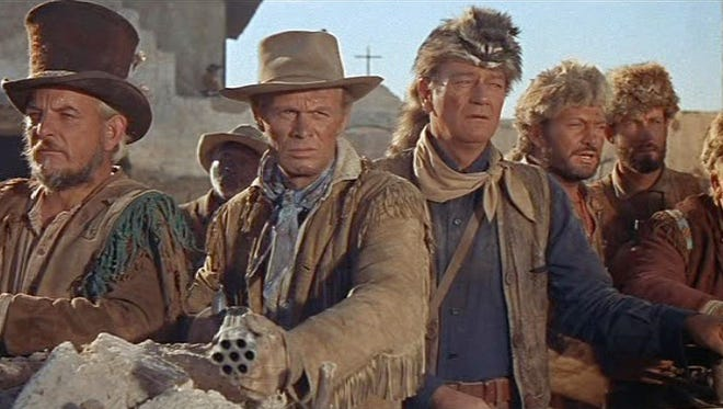 John Wayne (in coonskin cap) played Davy Crockett and Richard Widmark (with multibarreled gun) played Jim Bowie.