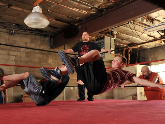 Silas Henson, 16, left, and Matthew Cruit practice falling in the ring Tuesday at a Total Nonstop Kids wrestling class in Lancaster.
