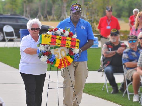Priscilla Southworth and Leonard Ross carry the wreath