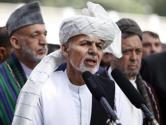 Afghan President Ashraf Ghani, center, addressing journalists