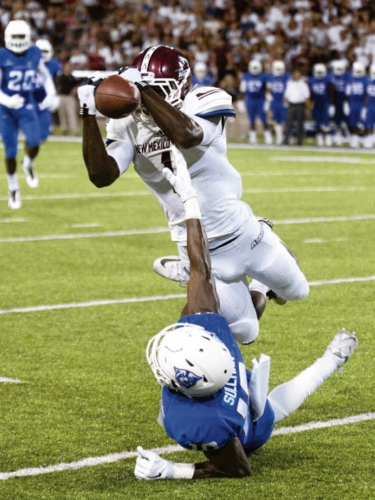 Gary Mook -- For the Sun-News   New Mexico State wide receiver Teldrick Morgan makes a play on the ball as Georgia State's Chandon Sullivan gets a hand in the play during the second quarter Saturday night at Aggie Memorial Stadium.