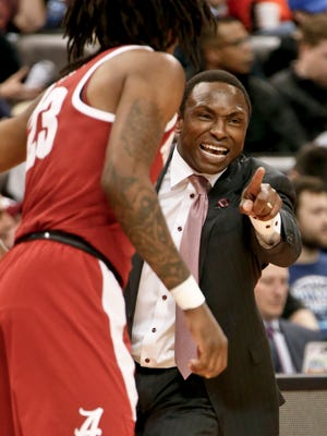 Alabama coach Avery Johnson, right, points toward the court while talking to John Petty against Virginia Tech, Thursday, March 15, 2018, in Pittsburgh.