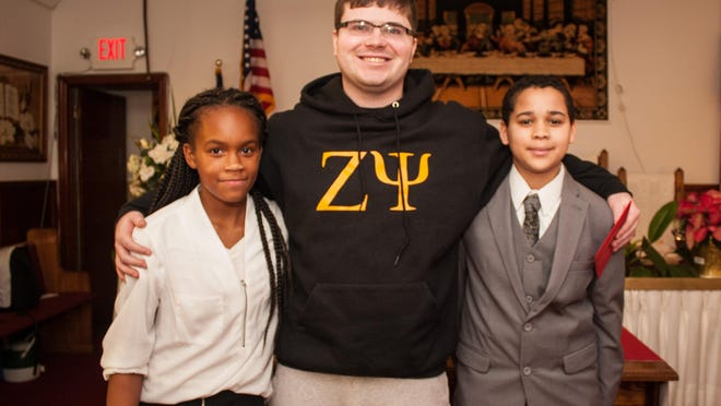 (L-R) Timmy McDonnell, middle, poses with Shalyse Williams (11), left, and Tyrone Harmen (14), right, who hands him a get-well card on behalf of the McLaughlin Pentecostal Faith Church, Sunday, Dec. 20, 2015, in Long Branch, New Jersey. (Contributor: EvaJo Alvarez)