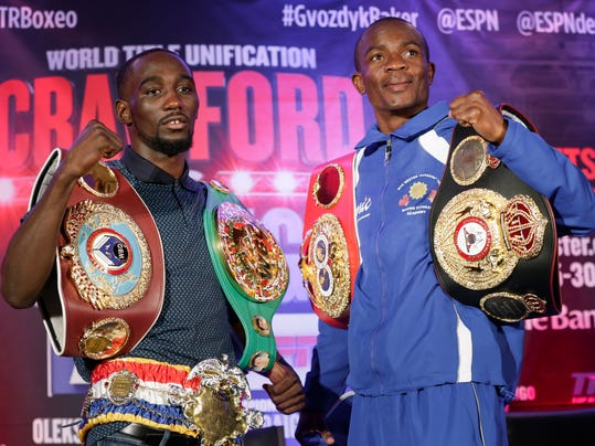 """Undefeated 140 pound world champions Terence """"Bud"""" Crawford (WBO and WBC champion), left, and Julius Indongo (IBF and WBA champion), pose with their championship belts during a news conference in Omaha, Neb., Thursday, Aug. 17, 2017. They will hold a world title unification fight on Aug. 19, 2017, in Lincoln, Neb., in only the second fight in the four-belt era in which all four titles will be on the line. (AP Photo/Nati Harnik)"""