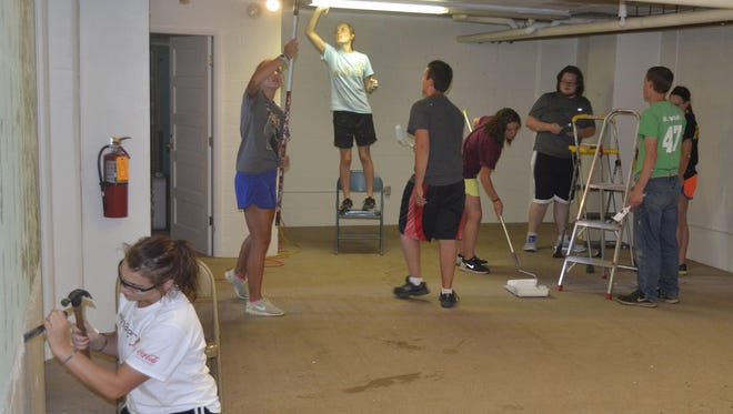 Members of a youth mission group from St. Patrick Catholic Church in Oak Grove, Minn., work on painting and other touch-ups Tuesday in the basement of the refurbished Upper Room Ministry Center at St. Jude Parish.