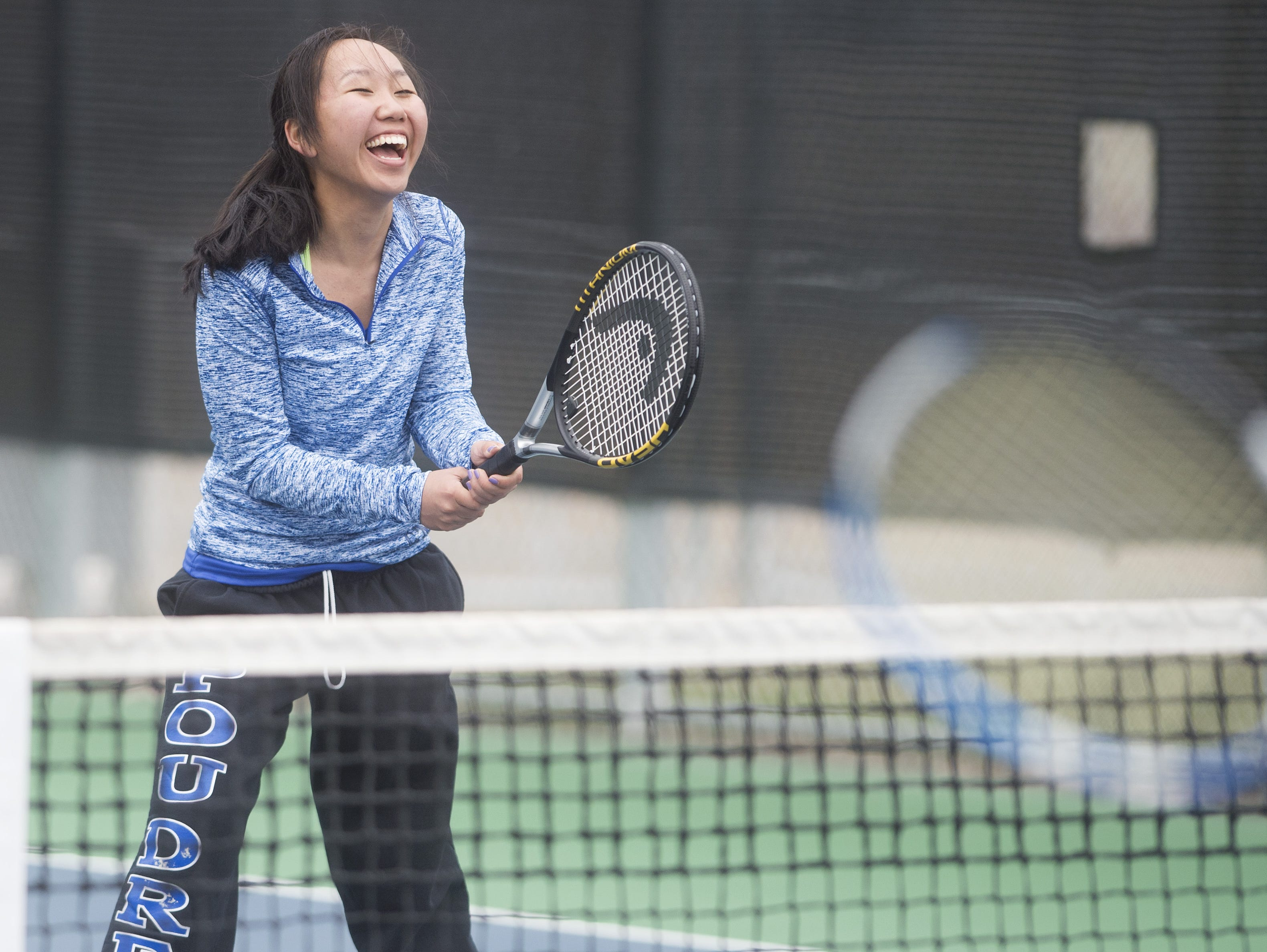 Mimi Mijidorj of Poudre cracks a smile in between sets while taking on a Rocky Mountain High School doubles team during a match Tuesday, March 29, 2016.