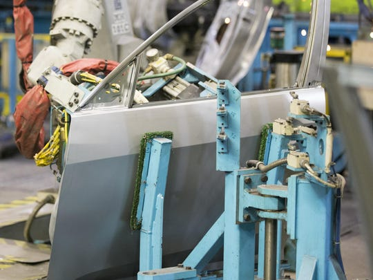 This file photo shows a robotic arm moving a door for a Honda Civic.