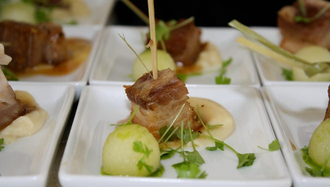 A pork belly morsel with a baby potato and local micro greens at the Naples Winter Wine Festival.
