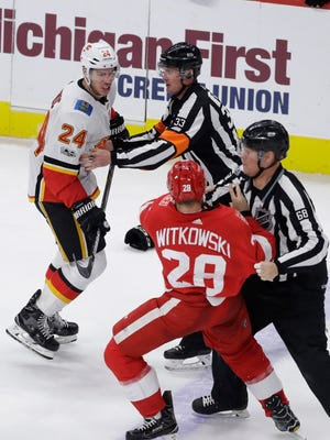 Linesman Scott Driscoll (68) pulls the Detroit Red Wings' Luke Witkowski away from the Calgary Flames' Travis Hamonic during the third period Wednesday night.