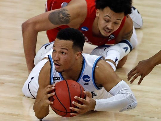 Villanova's Jalen Brunson (1), bottom, passes to a teammate after winning a scramble for the ball with Radford's Devonnte Holland, rear , during the first half of an NCAA men's college basketball tournament first-round game, in Pittsburgh, Thursday, March 15, 2018. (AP Photo/Gene J. Puskar)