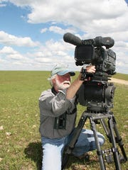 Timothy Barksdale of Choteau prepares his camera in Flint Hills, Kansas, one of the locations he filmed prairie chickens.