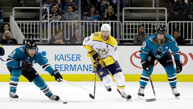 Nashville Predators' Mattias Ekholm (14) is defended by San Jose Sharks' Joe Pavelski, left, and Joe Thornton during the first period Wednesday.