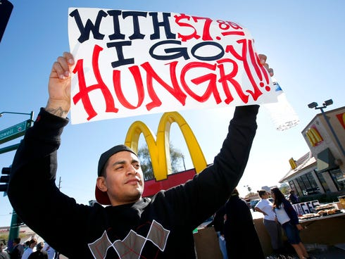 Alex Robles joins dozens of sign-holding protesters at a rally against low wages for fast-food workers, in front of a McDonald's on Dec. 5, 2013, in Phoenix.