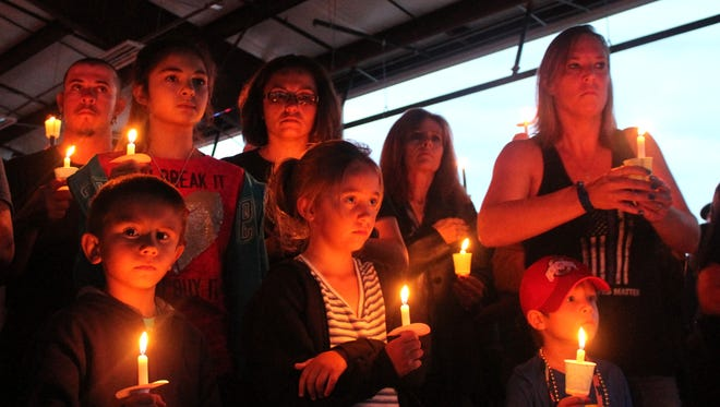 Local residents stand silently with their candles during the vigil for the fallen APD officer.