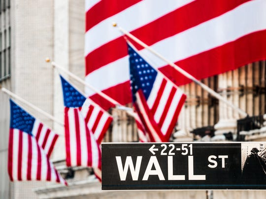 A large American flag covering the New York Stock Exchange, with the Wall Street sign in the foreground.