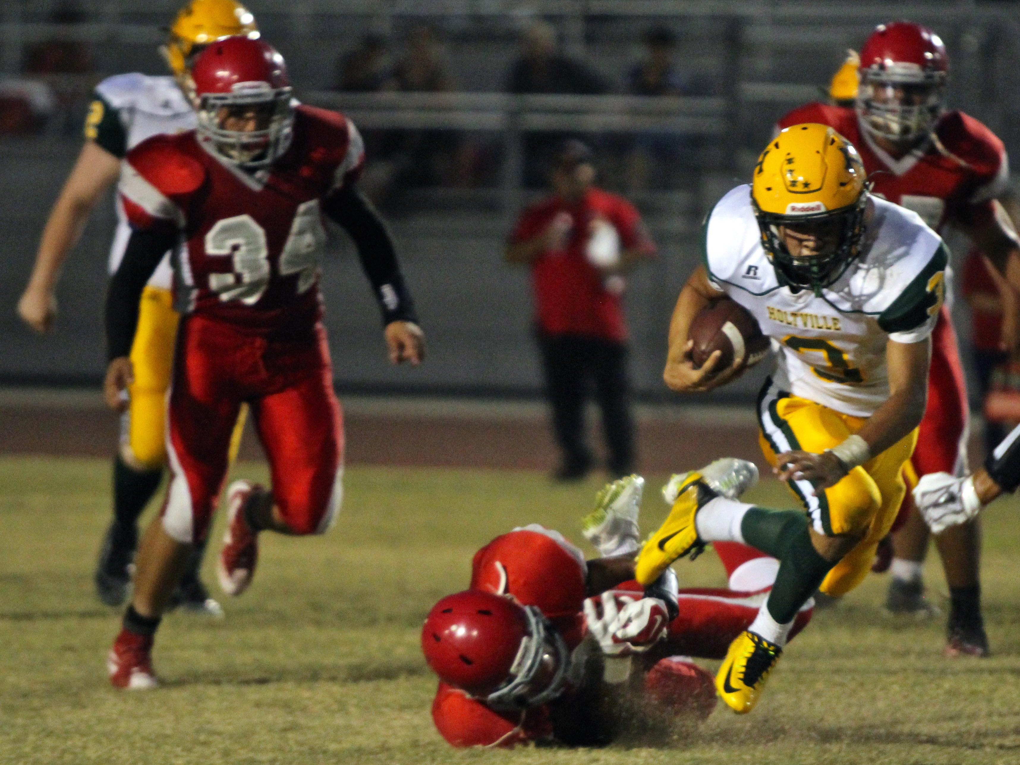 Holtville's Brice Bolin (3) attempts to elude a Desert Mirage defender during Friday night's game. Desert Mirage won 26-21.