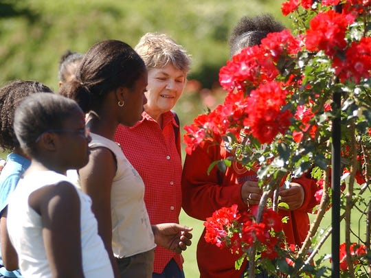 Looking back: Jane Grant pictured in the Maplewood Rose Garden with children from the neighborhood around Lake Avenue Baptist Church in Rochester on June 16 2004. Grant was retiring from her job educating children at the church.