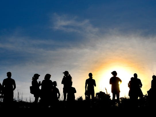 Spectators are silhouetted by the rising sun at the