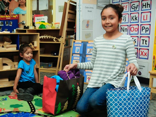 Lillyanna Martinez, 10, visits Jardin de los Niños students to give them  cold-weather gifts on Thursday. Martinez donated over 40 items for the children.