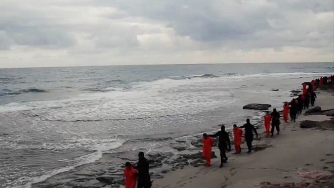This image made from a video released Sunday Feb. 15, 2015 by militants in Libya claiming loyalty to the Islamic State group purportedly shows Egyptian Coptic Christians in orange jumpsuits being led along a beach, each accompanied by a masked militant. Later in the video, the men are made to kneel and one militant addresses the camera in English before the men are simultaneously beheaded. The Associated Press could not immediately independently verify the video. (AP Photo)