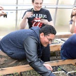Christopher Santana, 17, a student at Millville Senior High School, plants a sage seedling in a greenhouse during an Environmental Science II class.