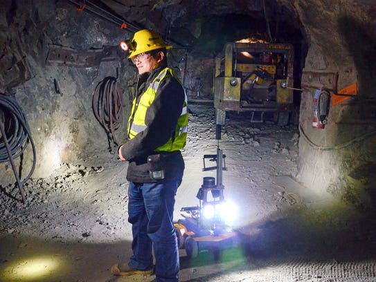A miner is backed by a robot in the Edgar Mine near