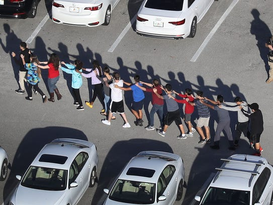 People are brought out of the Marjory Stoneman Douglas