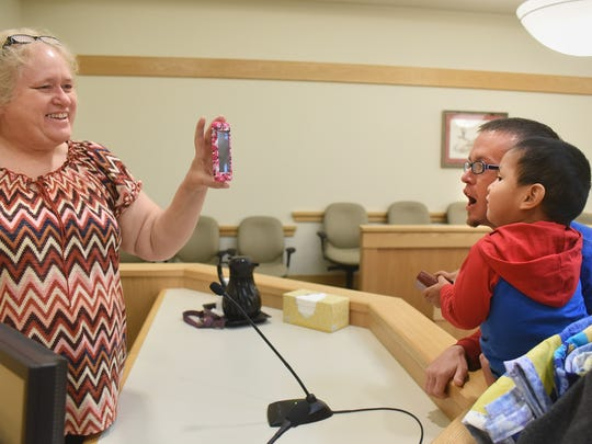 Randall Jeffrey and Theodore Jeffrey, 2, right, talk to family after the adoption ceremony on Friday Nov. 18, 2016, at the Eleventh Judicial District Court in Farmington. At left is Barbara Archuleta.