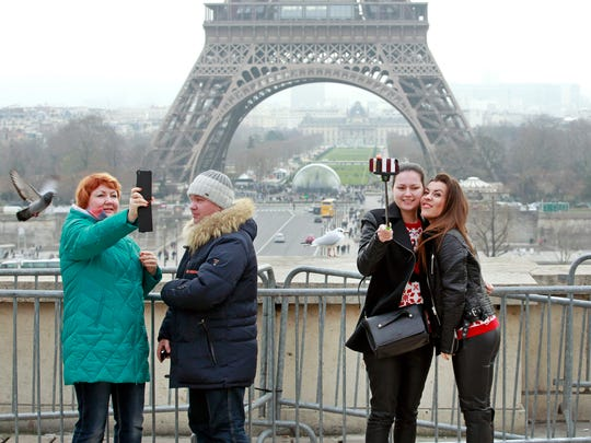 Tourists use a selfie stick on the Trocadero Square, with  the Eiffel Tower in background, in Paris, Tuesday, Jan. 6, 2015.
