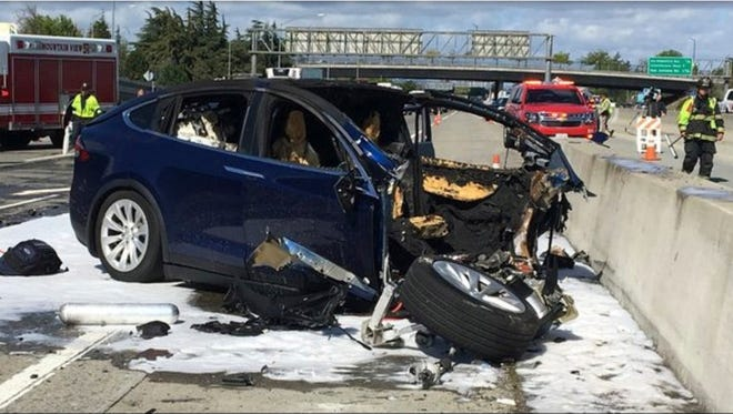 In this Friday March 23, 2018 photo provided by TV station KTVU, emergency personnel work a the scene where a Tesla electric SUV crashed into a barrier on U.S. Highway 101 in Mountain View, Calif.