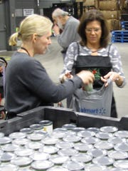 N.Y. Sen. Kirsten E. Gillibrand, D.N.Y., left, helps fill a bag held by Kim Frock, administrator of the Alternative School for Math & Science in Corning, at the Food Bank of the Southern Tier on Monday.