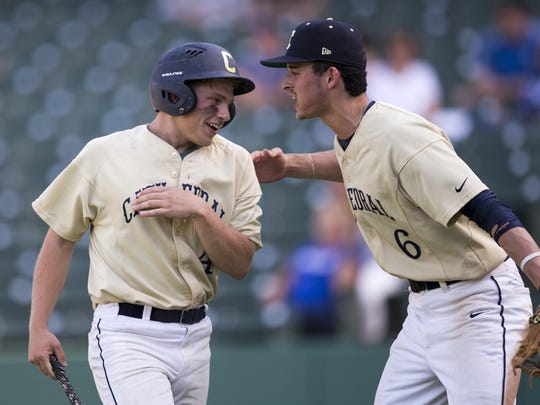 Ross Kirkpatrick (left), is congratulated on scoring a Cathedral High School run by teammate Kevin Flood, City Baseball Tournament, Victory Field, Indianapolis, Monday, May 15, 2017. Cathedral High School beat Heritage Christian High School, 8-3.