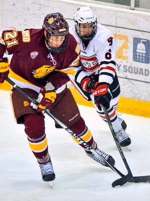St. Cloud State's Daniel Tedesco (6) battles Minnesota-Duluth's Carson Soucy (21) for control of the puck in the first period Friday, Nov. 7 at Herb Brooks National Hockey Center.