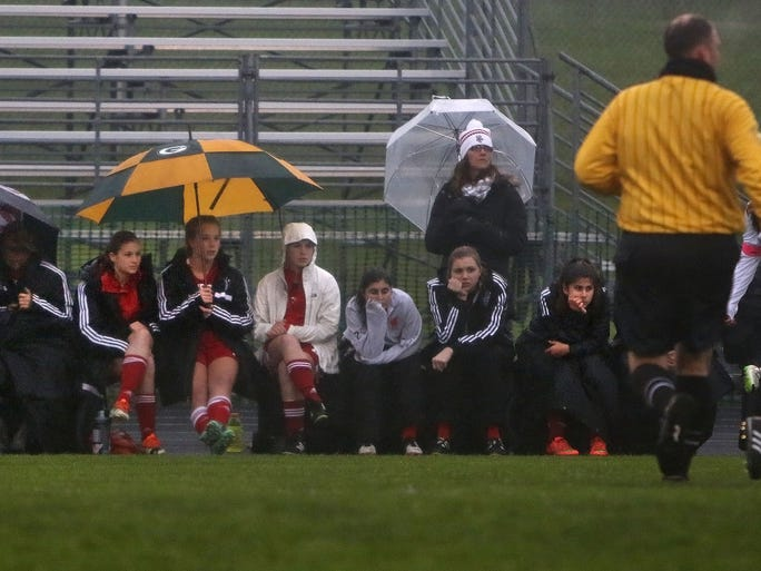 As a steady rain falls, the Homestead bench looks on during the first half  of the varsity soccer teams game against Nicolet at Nicolet High School Tuesday, May 10, 2016, in Glendale, Wisconsin.